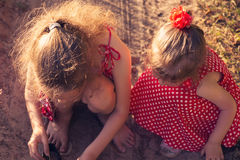 Two little sisters play with sand in park on a sunny summer day. Stock Images