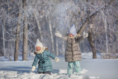 Two little sisters play and throw up a snow in winter Royalty Free Stock Images