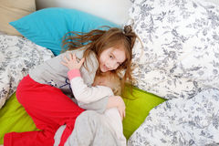 Two little sisters playing in bed Royalty Free Stock Photos
