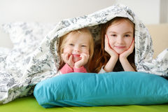 Two little sisters playing in bed Stock Image
