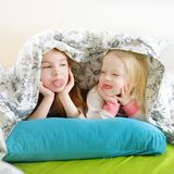Two little sisters playing in bed Stock Photography