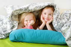 Two little sisters playing in bed Royalty Free Stock Image