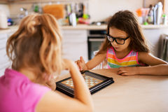 Two little sisters playing chess. Two beautiful little sisters playing chess on a Tablet PC royalty free stock photos