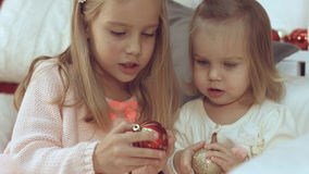 Two little sisters playing with Christmas balls while sitting on the couch Stock Photos