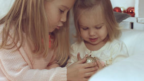 Two little sisters playing with Christmas balls while sitting on the couch Royalty Free Stock Image