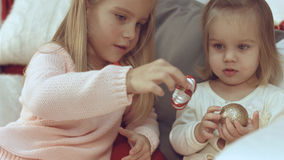 Two little sisters playing with Christmas balls while sitting on the couch Royalty Free Stock Photos