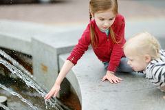 Two little sisters playing with a city fountain Stock Photography
