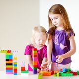 Two little sisters playing with colorful blocks Stock Image