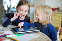 Two little sisters playing with a digital tablet Royalty Free Stock Photography