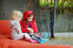 Two little sisters playing with a digital tablet Royalty Free Stock Photo