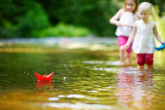 Two little sisters playing with paper boats Royalty Free Stock Images