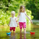 Two little sisters playing with paper boats Stock Photos