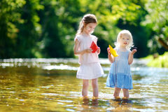 Two little sisters playing with paper boats Stock Image