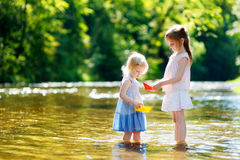 Two little sisters playing with paper boats Stock Images