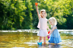 Two little sisters playing with paper boats Royalty Free Stock Photo