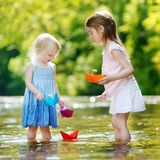 Two little sisters playing with paper boats Royalty Free Stock Photos