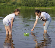 Two little sisters playing with paper boats by a river on warm a Royalty Free Stock Photography