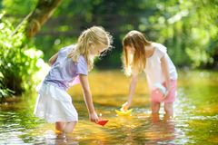 Two little sisters playing with paper boats by a river on warm and sunny summer day. Children having fun by the water. Summer activities for small kids stock photo