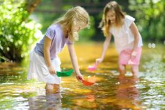 Two little sisters playing with paper boats by a river on warm and sunny summer day. Children having fun by the water. Summer activities for small kids royalty free stock images