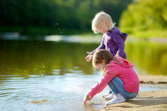 Two little sisters playing by a river Stock Image