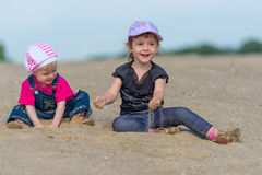 Two little sisters playing in the sand on the beac Royalty Free Stock Photography