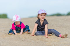 Two little sisters playing in the sand on the beac Royalty Free Stock Image