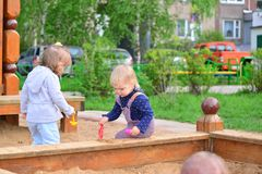 Two little sisters playing in sandbox royalty free stock photo