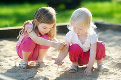 Two little sisters playing in a sandbox Stock Photos