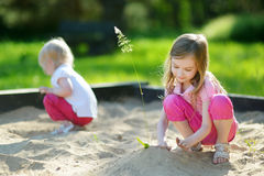 Two little sisters playing in a sandbox Royalty Free Stock Photo
