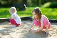 Two little sisters playing in a sandbox Royalty Free Stock Photos