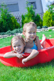 Two little sisters playing and splashing in the. Pool on a hot sunny day. This image has attached release Stock Photography
