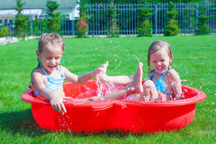 Two little sisters playing and splashing in the. Pool on a hot sunny day. This image has attached release Stock Photo