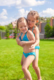 Two little sisters playing and splashing in the. Pool on a hot sunny day. This image has attached release Royalty Free Stock Photo