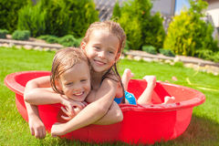 Two little sisters playing and splashing in the. Pool on a hot sunny day. This image has attached release Stock Photos