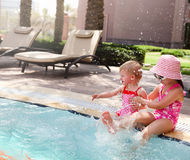 Two little sisters playing in swimming pool Royalty Free Stock Images