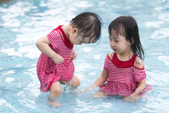 Two Little Sisters Playing in Water Royalty Free Stock Image