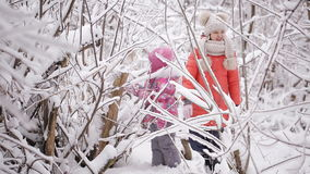 Two little sisters playing in the winter woods between snow-covered trees. The blind girl sees nothing stock footage