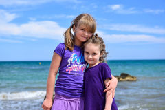Two little sisters posing on the beach Stock Photos