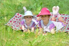 Two little sisters resting on plaid in nature Royalty Free Stock Photography