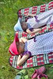 Two little sisters resting on plaid in nature Stock Image
