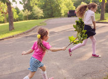 Two little sisters run and play on the road in the park on a war Stock Photo