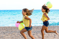 Two little sisters running together on beach. Stock Photography