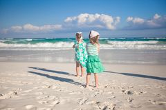 Two little sisters running at tropical beach in Stock Photos