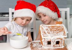 Two little sisters in santa hat making biscuit house Royalty Free Stock Image