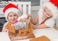 Two little sisters in santa hat making biscuit house Stock Image