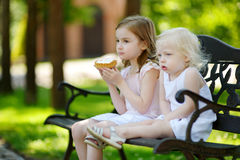 Two little sisters sharing delicious cream tart Stock Photo