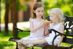 Two little sisters sharing delicious cream tart Stock Images