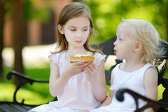 Two little sisters sharing delicious cream tart Royalty Free Stock Photo