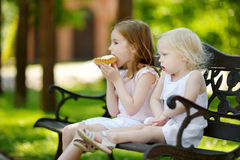 Two little sisters sharing delicious cream tart Stock Photos
