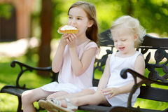 Two little sisters sharing delicious cream tart Royalty Free Stock Image